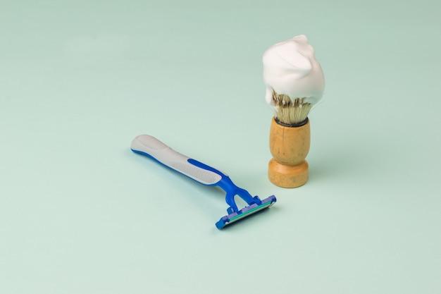 Een scheerkwast met schuim en een wegwerpscheermesje op een blauwe ondergrond