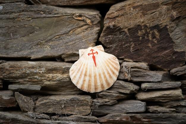 Een schelp met een geschilderd rood kruis een symbool van de camino de santiago bovenop enkele stenen