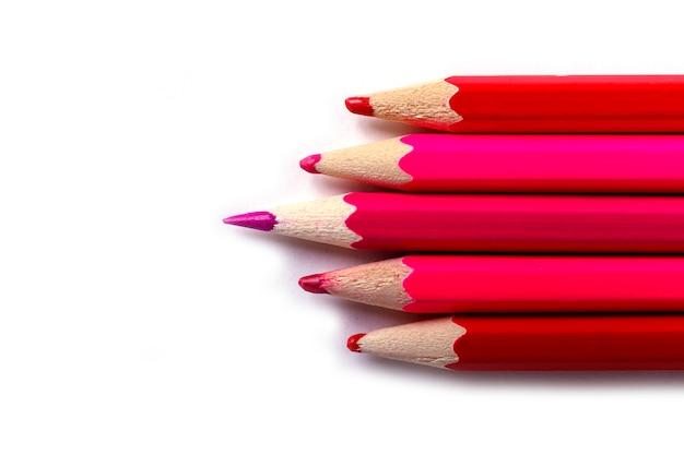 Een scherp potlood dat opvalt ten opzichte van de botte. het is gemakkelijk om mooi te zijn als je niets doet. rode potloden op wit.
