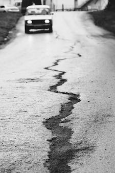 Een scheur in het asfalt en een reizende auto aan de voorkant.
