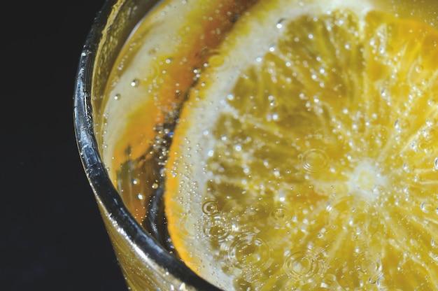 Een schijfje sinaasappel bedekt met bubbels ligt in een glas bruisend water. detailopname.