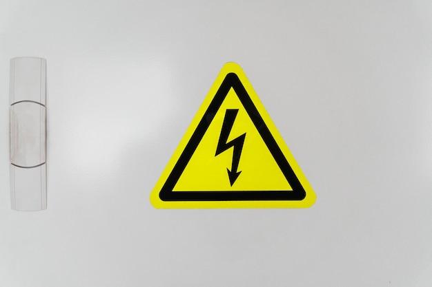 Een schild met een gele driehoek en een bliksemschicht duidt op hoogspanning