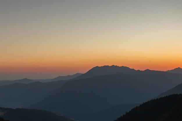Een schilderachtige zonsondergang in de bergen met zonlicht, mooi licht. avond zomer landschap in een vallei met horizon, lucht, gras, bloemen. foto achtergrond natuur panorama