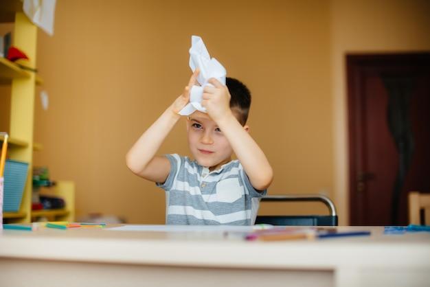Een schoolgaande jongen maakt thuis huiswerk.