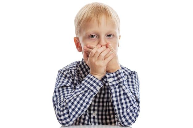 Een schooljongen in een blauw geruit overhemd bedekte zijn mond met zijn handen.