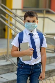Een schooljongen in een wit overhemd, een blauwe das en een rugzak staat in een medisch masker met een tablet
