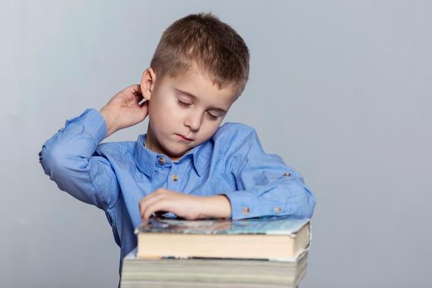 Een schooljongen maakt huiswerk aan de tafel. verdriet en vermoeidheid door studeren. grijs.