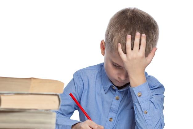 Een schooljongen maakt huiswerk aan de tafel. verdriet en vermoeidheid door studeren. over wit wordt geïsoleerd.