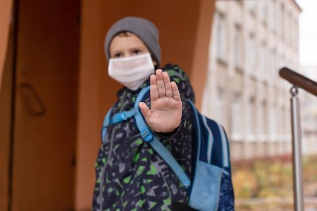 Een schooljongen met een beschermend masker toont zijn hand stop