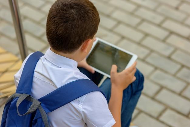 Een schooljongen met een blauwe rugzak zit op de trap en speelt een tablet. achteraanzicht