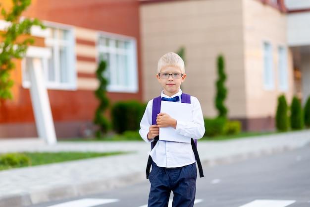 Een schooljongen met een blonde bril met een rugzak en een wit boek staat op de school. dag van de kennis