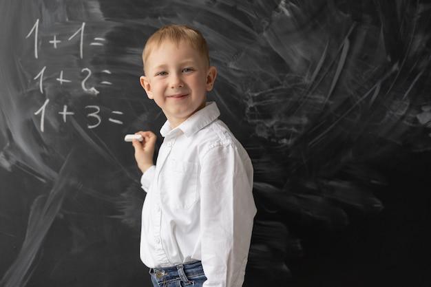 Een schooljongen staat voor het bord in de klas en schrijft voorbeelden in wiskunde. de jongen lacht. positieve student in de les. terug naar school. wiskundeles op de basisschool.