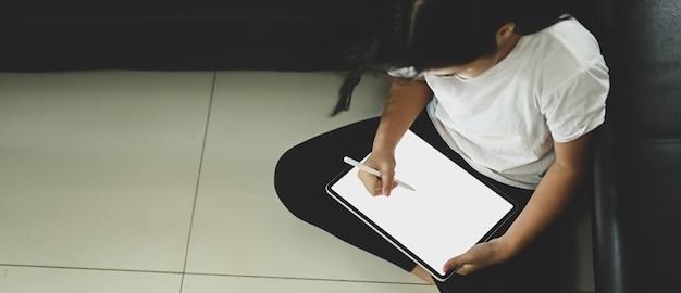 Een schoolmeisje gebruikt een witte lege tablet van de schermcomputer en een styluspen in de woonkamer.