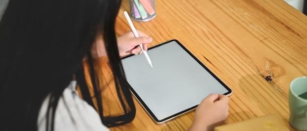 Een schoolmeisje gebruikt een witte lege tablet van de schermcomputer en een styluspen in de zitkamer.