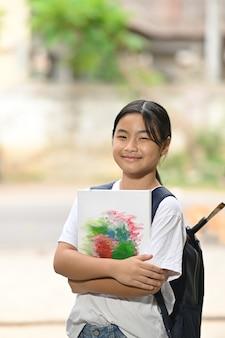 Een schoolmeisje houdt schildersbenodigdheden vast en draagt een schooltas terwijl ze staat te wachten op een schoolbus.