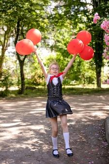 Een schoolmeisje in een witte blouse met een rode stropdas, met een strik en rode ballonnen in de klas. terug naar school-concept.