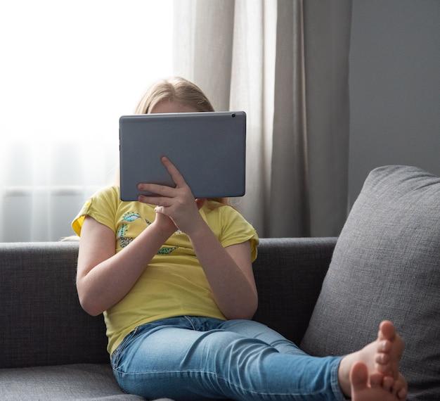 Een schoolmeisje in spijkerbroek en een geel t-shirt op de bank thuis kijken naar een online les op de laptop. afstandsonderwijs tijdens het coronavirus