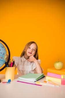 Een schoolmeisje in uniform zit aan een tafel met schoolspullen op een gele achtergrond