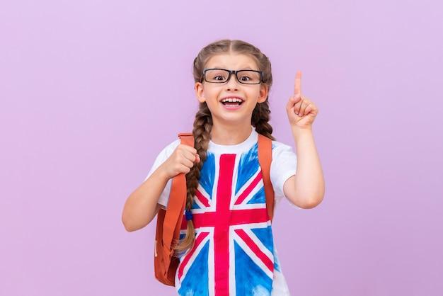Een schoolmeisje met een afbeelding van de engelse vlag op een t-shirt met een bril wijst met haar vinger naar de bovenkant. engels leren. geïsoleerde achtergrond.