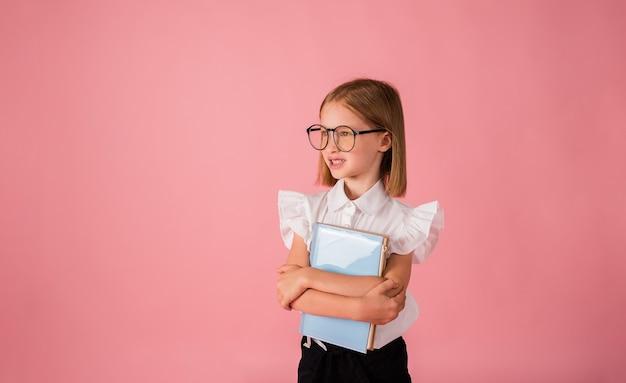 Een schoolmeisje met een bril en een uniform heeft een blauw notitieboekje op een roze achtergrond met een plek voor tekst