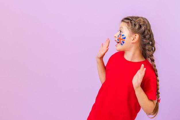 Een schoolmeisje met een engelse vlag kijkt erg verbaasd naar de zijkant. geïsoleerde achtergrond. studie studie van vreemde talen