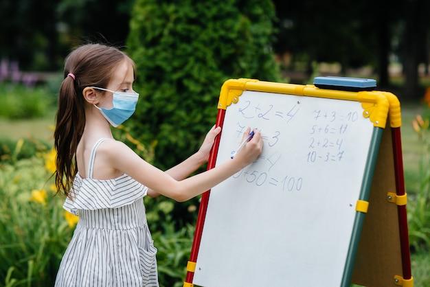 Een schoolmeisje met een masker staat en schrijft lessen op het whiteboard