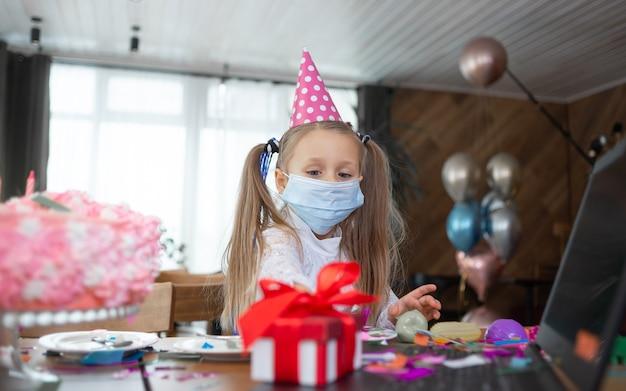 Een schoolmeisje met een medisch masker en een feestelijk pet staat bij de tafel. het meisje kijkt naar het cadeau.