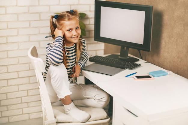 Een schoolmeisje met koptelefoon zit aan een tafel in de buurt van een computer thuis en maakt huiswerk