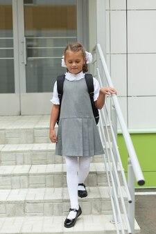 Een schoolmeisje met rugzak loopt naar beneden