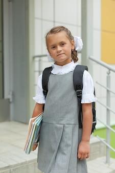 Een schoolmeisje met schoolboeken en een rugzak loopt in de buurt van de school
