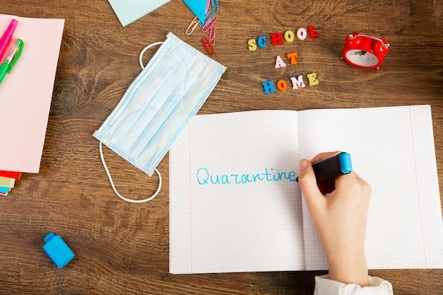 Een schoolmeisje schrijft het woord quarantaine met een stift in een notitieboekje. plat leggen