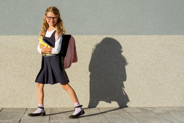 Een schoolmeisje van basisschool met notitieboekjes in zijn hand.