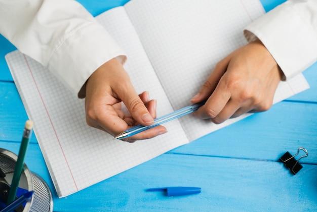 Een schoolmeisje zit aan een bureau met een pen op een blauwe ruimte.