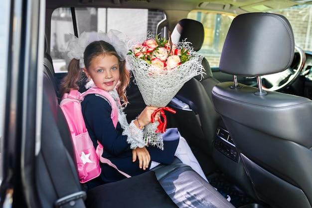 Een schoolmeisje zit op 1 september in de auto van haar ouders. papa brengt een klein meisje naar school met een bos bloemen.