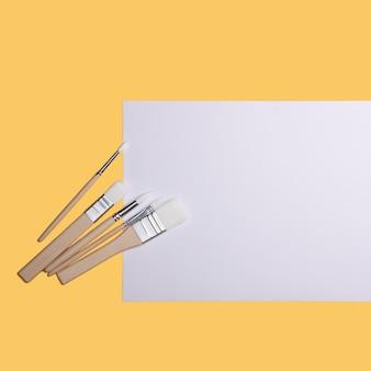 Een schoon wit vel en verfborstels op een gele achtergrond met een plek om te kopiëren