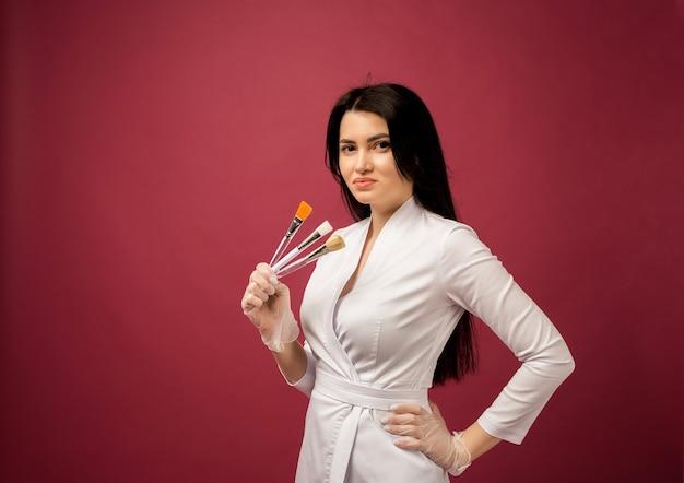Een schoonheidsspecialiste in een wit medisch pak houdt bordeauxrode kwastjes vast
