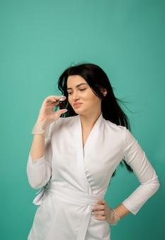 Een schoonheidsspecialiste in een wit pak en doorzichtige handschoenen houdt een medicijn op turkoois