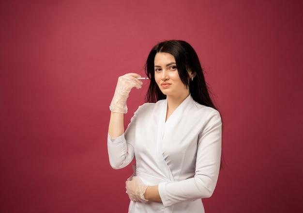 Een schoonheidsspecialiste in een wit pak en transparante handschoenen houdt een botox-spuit vast op bordeauxrood