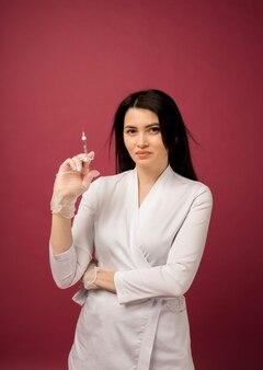 Een schoonheidsspecialiste in een wit uniform houdt een injectiespuit op bordeauxrood vast