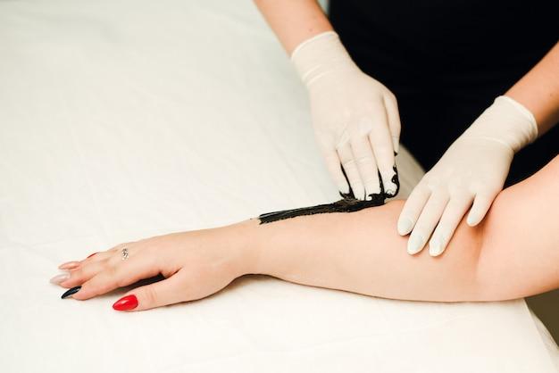 Een schoonheidsspecialiste maakt haarverwijdering voor een schone, mooie huid zonder haar. ontharing met zwarte was.