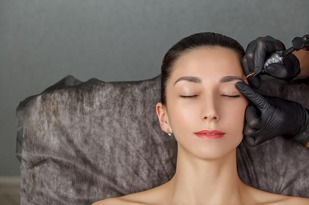 Een schoonheidsspecialiste voert het maken van permanente wenkbrauwen uit. permanente make-upbehandeling.