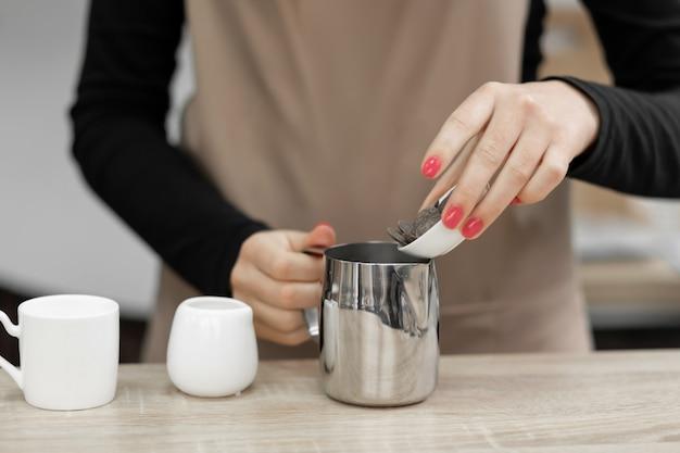 Een schortbarista giet warme chocolademelk in een kopje. barista werkt in een koffieshop