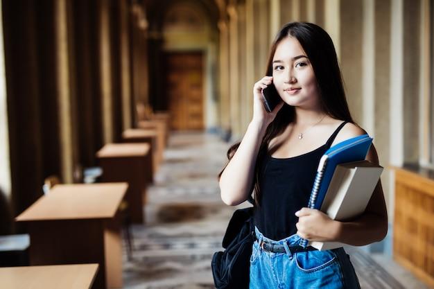 Een schot van een aziatische student die op de telefoon op universiteit spreekt