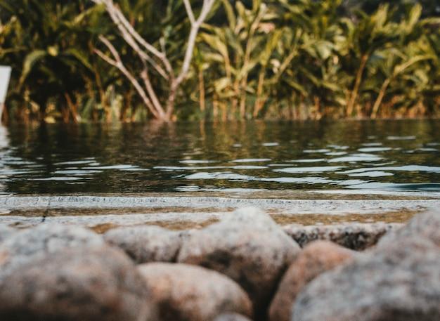 Een schot van een meer met rotsen vooraan en groen