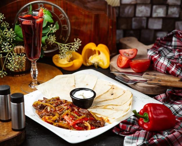 Een schotel fajitas van rundvlees geserveerd met flatbread en saus