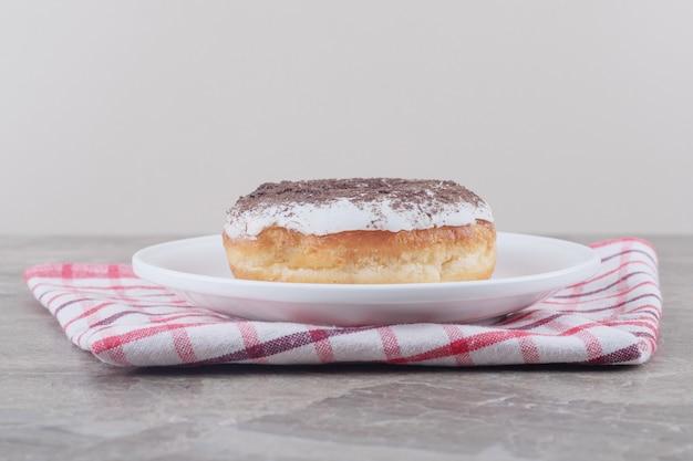 Een schotel met een donut op een handdoek op marmer