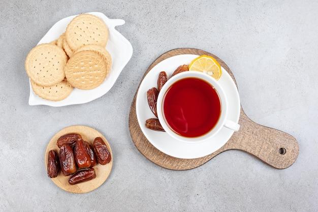 Een schotel met koekjes en een kleine stapel dadels naast een kopje thee met enkele dadels op schotel op een houten bord, op marmeren oppervlak