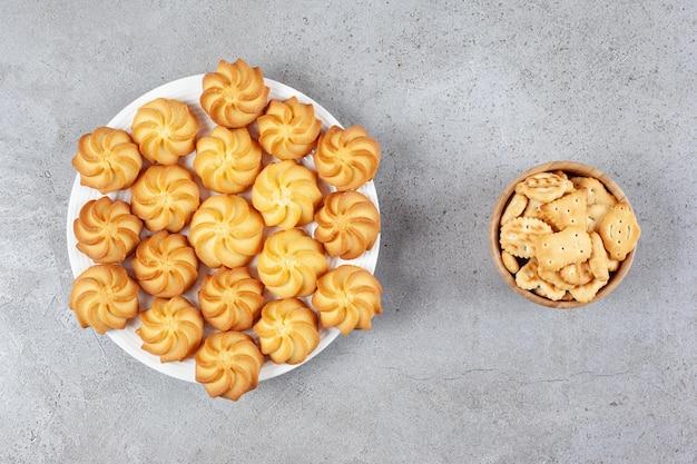 Een schotel met koekjes naast een schaaltje met crackers op een marmeren ondergrond