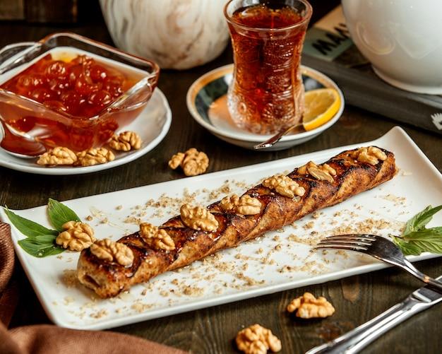 Een schotel met lula kebab gegarneerd met walnoot