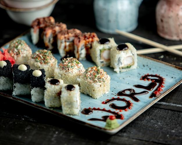 Een schotel sushibroodjes met zalm zwarte tobiko tempura